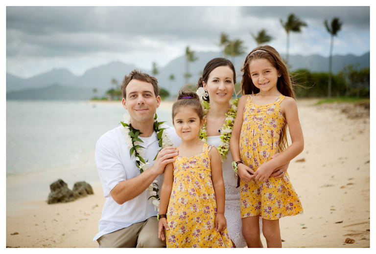 wedding photo of bride and groom with flower girls on Kualoa Beach
