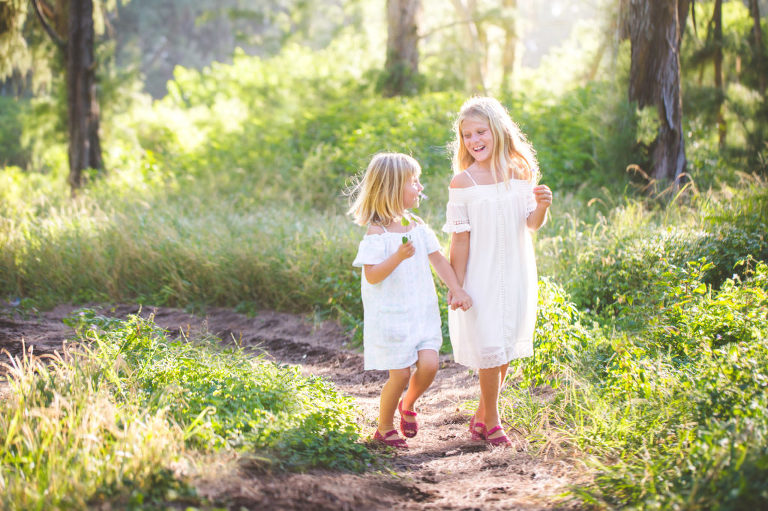 playful and natural photo of girls in hawaiian forest